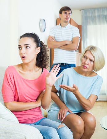 squabble: Adult girl having quarrel with husband and mother-in-law Stock Photo