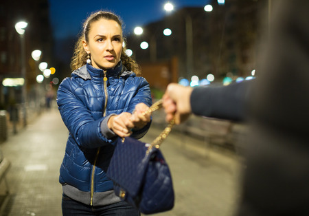 accosting: Night street robbery scene: man taking away young woman bag Stock Photo