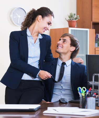 Top manager flirting with happy american adult subordinate official at workplace