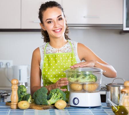 Sonriente joven ama de casa con brócoli, papa y vapor moderno. Foto de archivo - 76542109