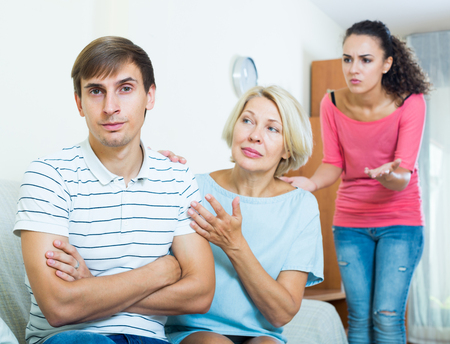 Senior mother-in-law trying to reconcile young couple indoors