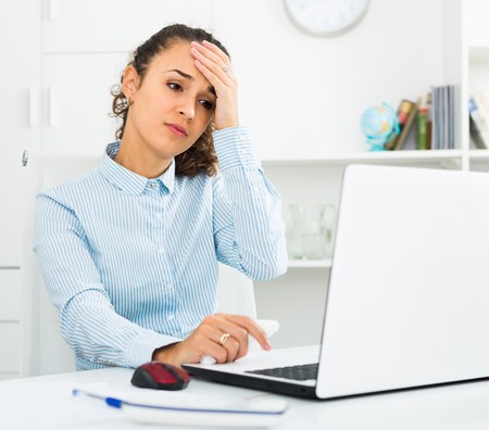Exhausted young woman with headache working at laptop in office Stock Photo