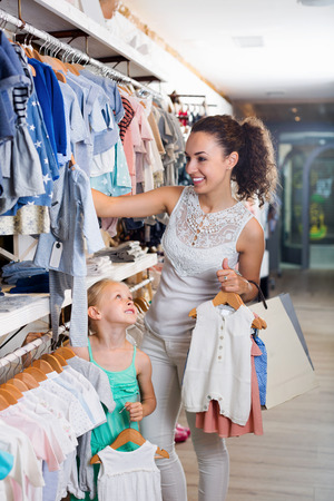 Young cheerful mother with daughter girl choosing clothes in kids apparel boutique Stock Photo