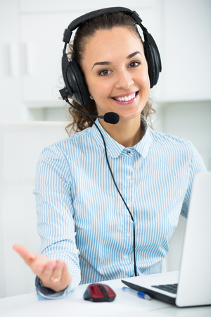 Portrait of young woman with headset working in call center