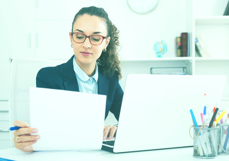 Smiling woman working with paperwork and laptop in office Stock Photo