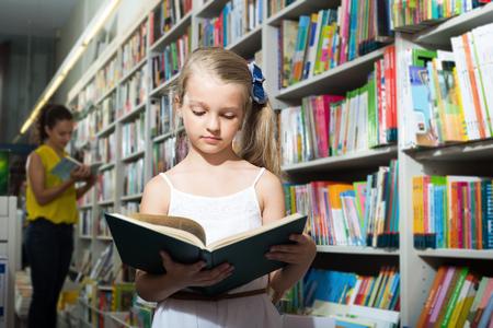 Girl in school age taking open chosen book in shop