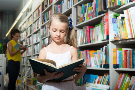 Girl in school age taking open chosen book in shop