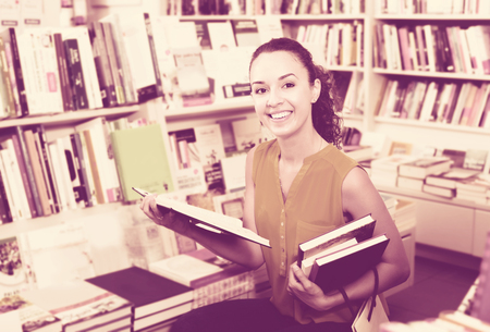 publishers: Portrait of glad young woman looking interested and reading textbook in book store Stock Photo