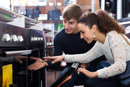 Positive couple choosing kitchen oven in store and smiling Stock Photo - 76542728