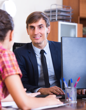 Smiling businessman talking with potential client at the table in office
