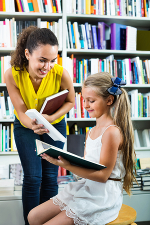 Young cheerful woman giving book to girl in school age in bookstore