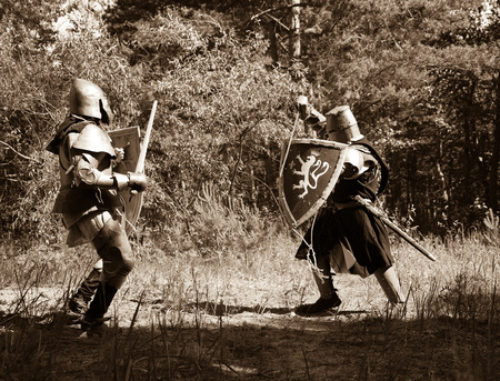 Two knights in armor is fighting  at forest Stock Photo