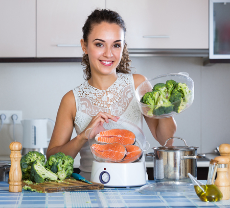 jorobado: Happy adult girl steaming salmon and vegetables in domestic kitchen