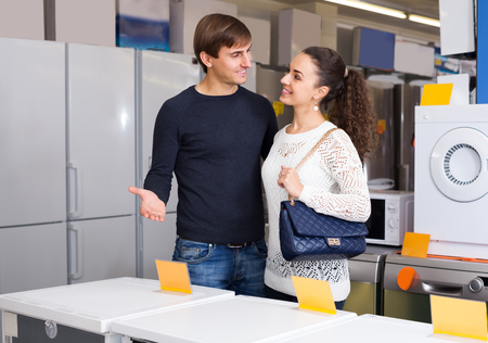 hobs: Portrait of young couple at household appliances section of supermarket