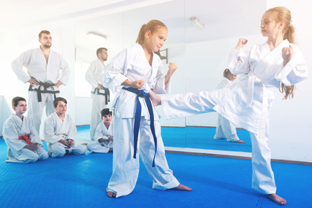Females are trying in sparring to use new moves at karate class.