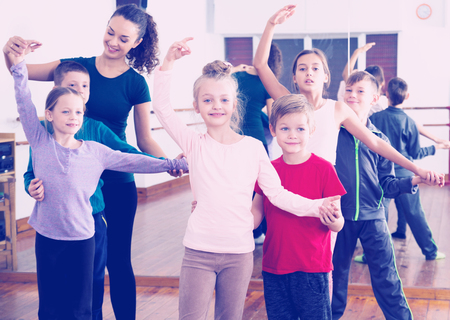 hustle: Happy little boys and beautiful girls having dancing class and their teacher Stock Photo