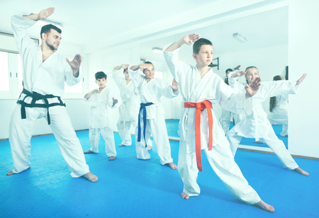 child protection: Children trying new martial moves in the practice during a karate class