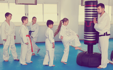 child protection: Diligent children training karate kicks on punching bag during karate class