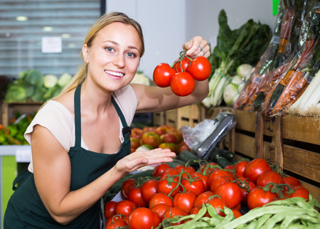 positive young woman seller showing fresh ripe tomatoes in food store