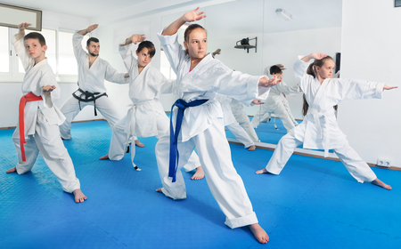 child protection: Children trying new martial moves in practice during karate class in a gym
