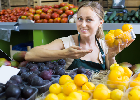 Portrait of young woman selling ripe fresh plums on fruit market Stock Photo