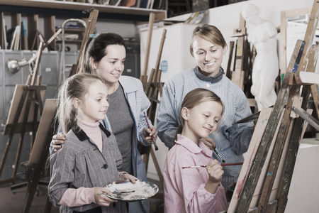 Young woman students appraising work of their group mate during class at art studio Stock Photo