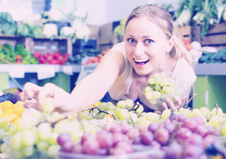 ?positive young woman customer choosing grapes on market