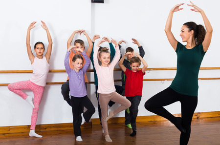 concentrated boys and girls primary school age rehearsing ballet dance in studio Stock Photo - 76565523