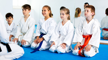 child protection: Glad children enjoying their trainings with coach at karate class