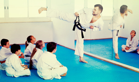 child protection: Glad male coach explaining new maneuvers to children in karate class
