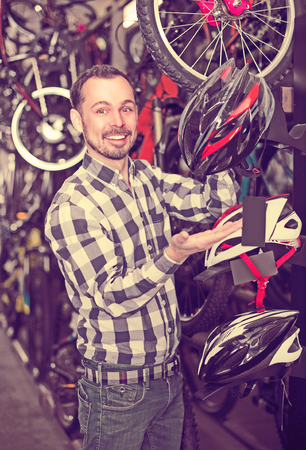 27 years old: Man 27-36 years old is choosing for himself comfortable helmet for driving bicycle. Stock Photo