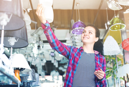 Young woman in shop of home appliances choosing modern and stylish pendant lamp for home