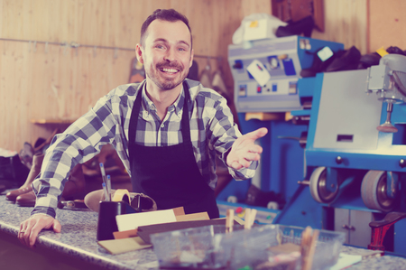 attentiveness: Handsome male worker showing his workplace and tools in shoe repair workshop Stock Photo