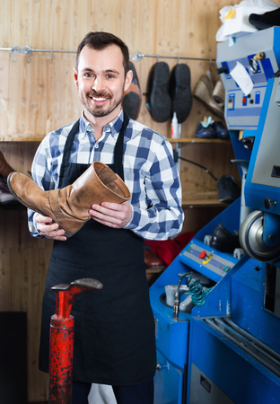 resulted: Smiling  friendly  male worker demonstrating repaired shoes in shoe repair workshop