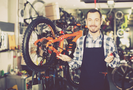 qualitatively: Happy young man working on master mechanic assembling bicycle equipment