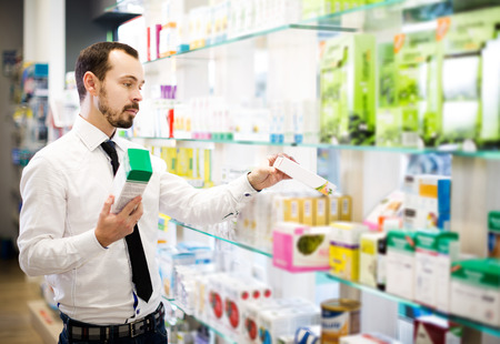 Adult customer searching for reliable drug in pharmacy Stock Photo