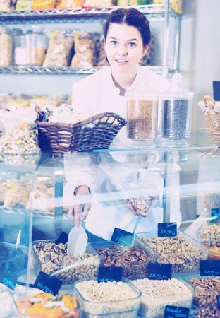Smiling girl offers a variety of nuts in the department of sweets
