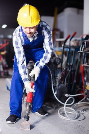 Positive man worker using jackhammer for work at industry