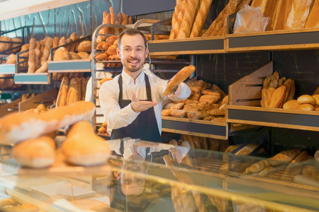 positive english male shop assistant demonstrating delicious loaves of bread in bakery Stock Photo