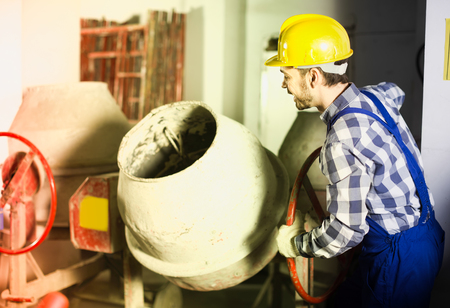 Positive male worker using concrete mixer for construction work at workshop