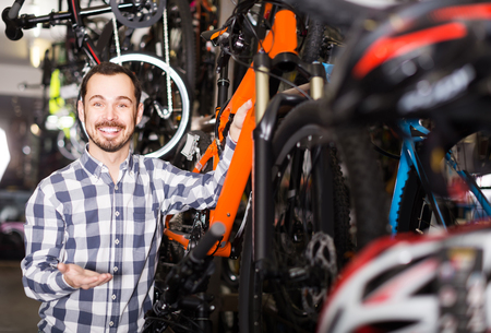 qualitatively: smiling man in sports workshop mounts bike using special tools
