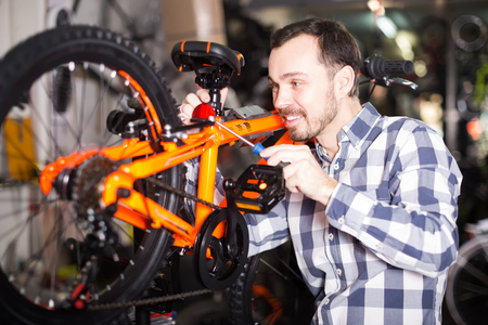 smiling male mounts bicycle parts for assembly bike in sports shop