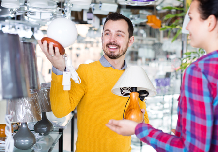 Adult man and girl in lighter shop choose stylish and modern lamp for house interior Stock Photo