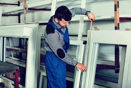 Professional diligent friendly smiling labour with finished PVC profiles and windows at factory Stock Photo