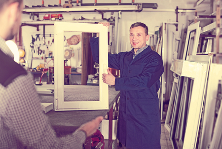 Glad careful adult workman showing PVC manufacturing output in workshop Stock Photo