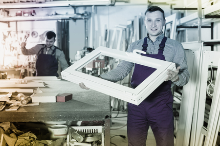 Engineer is demonstrating the window frame in workshop.