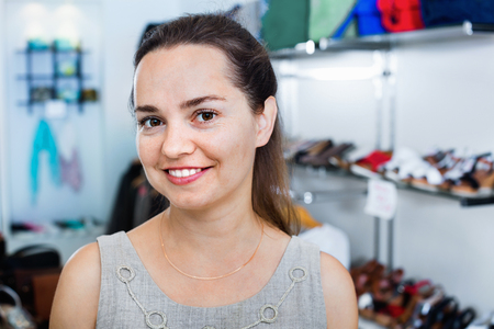 Cheerful friendly smiling young brunette offers footwear in fashion shoes center