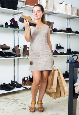 joyful young female customer selecting loafers in footgear center Stock Photo