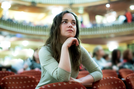 Portrait of beautiful girl sitting in theatre salon and watching show