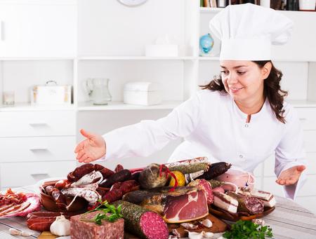 hams: Chef niña cuesta cerca de la mesa con productos ahumados y salchichas y tiene en la mano con jamon placa